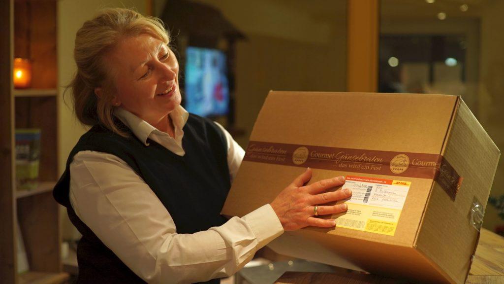 Eine Kundin, die ein Paket von Gourmetgänsebraten in den Händen hält.